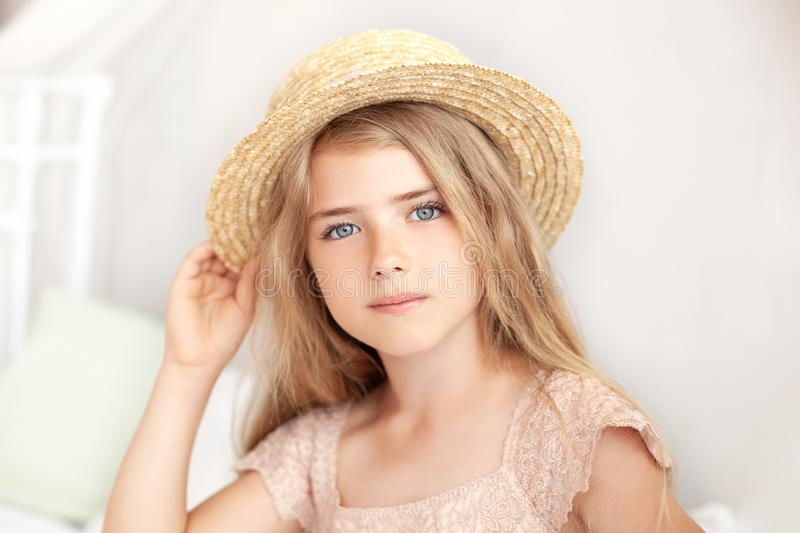 Portrait of a cute girl in a straw hat. Thoughtful little blonde with long hair sits on the bed in a bright children`s room. Child stock photos