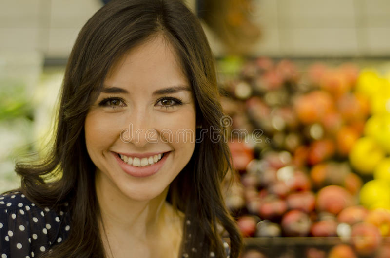 Portrait of a cute girl at the supermarket. Cute young woman buying fruits and vegetables at the grocery store stock photos