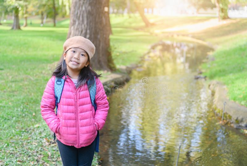 Portrait of cute girl wear pink down jacket at park, stock images