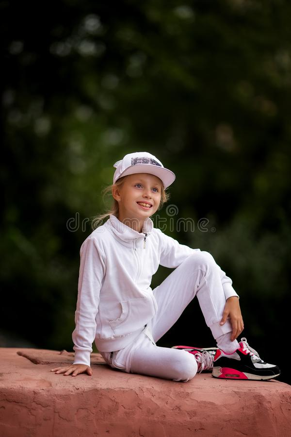 Portrait of a cute girl in a white tracksuit. Active and energetic girl having fun in summer. The concept of sports, dance, hip stock photos