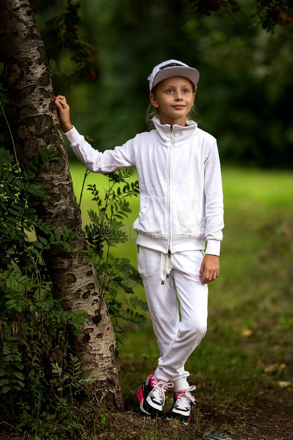Portrait of a cute girl in a white tracksuit. Active and energetic girl having fun in summer. The concept of sports, dance, hip royalty free stock photography