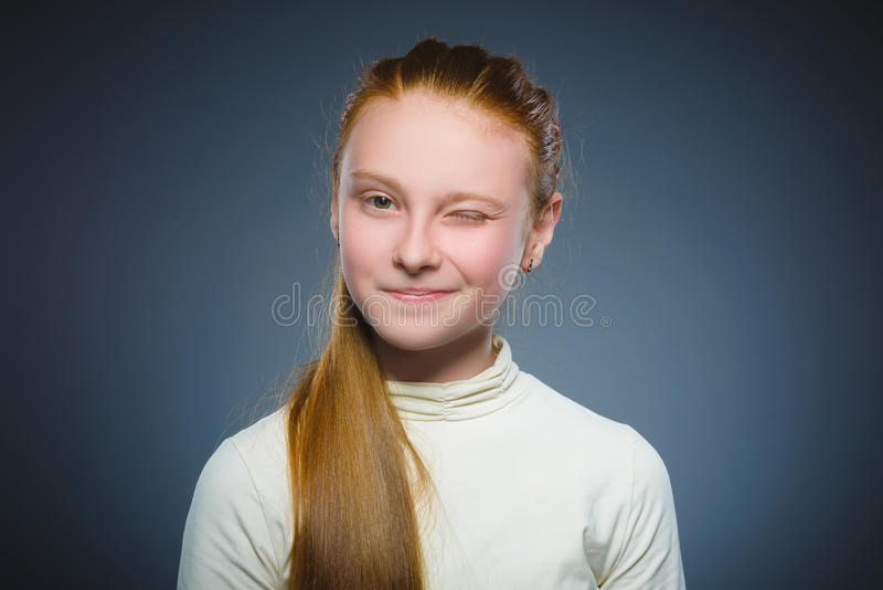 Portrait of cute girl winking over gray background. Looking at the camera royalty free stock images