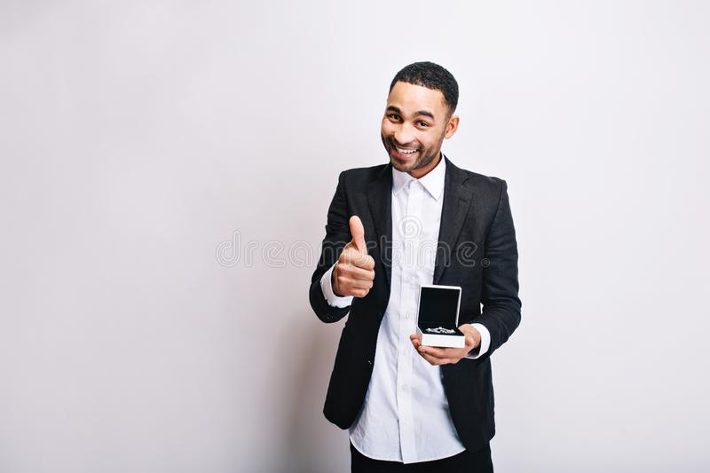 Portrait cute handsome guy in white shirt, black jacket with gift in hands smiling to camera on white background stock photo