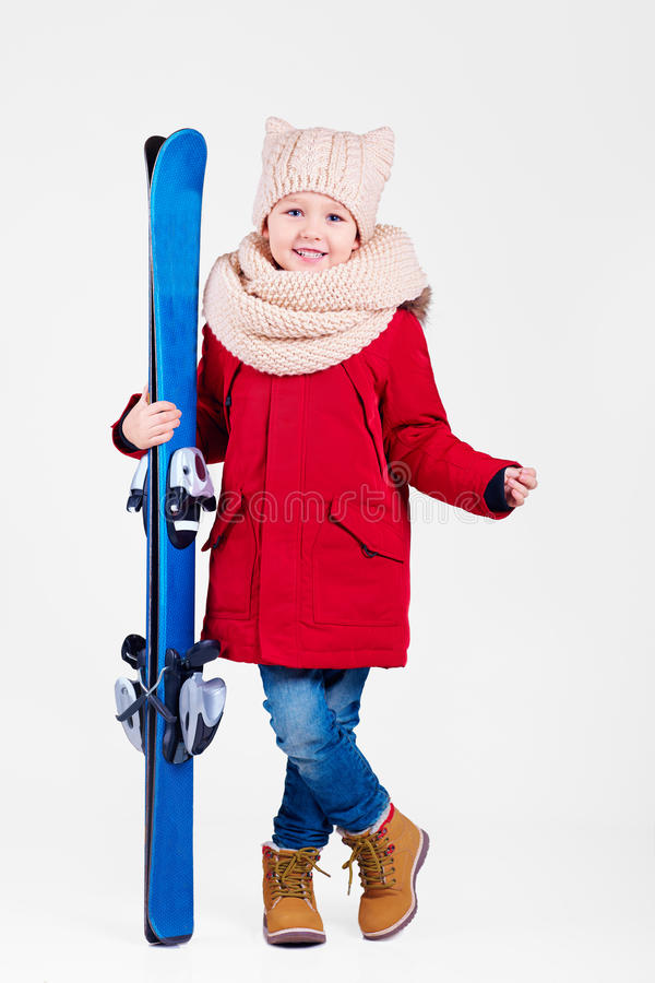 Portrait of cute happy boy holding skis in hands stock photos