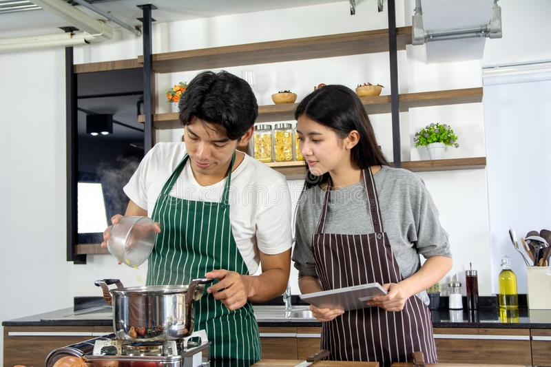 Portrait of cute happy couple in apron in selfie action posting with tablet while guy preparing cooking decorated with vegetable royalty free stock photo