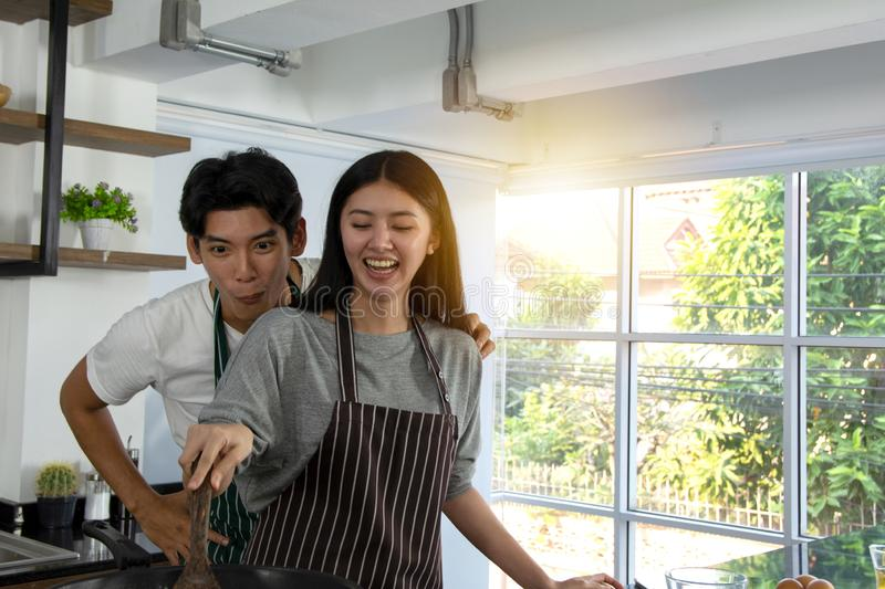 Portrait of cute happy couple in apron in selfie in cheerful action holding turner preparing cooking brekafast in modern kitchen stock photos