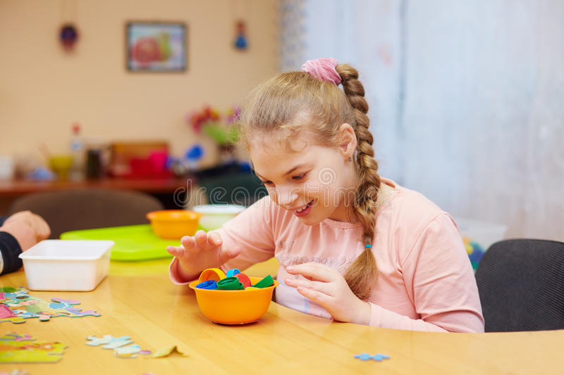 Portrait of cute happy girl with disability develops the fine motor skills at rehabilitation center for kids with special needs. Cute happy girl with disability royalty free stock images