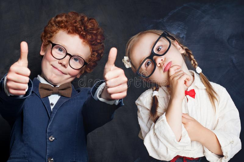 Portrait of cute happy kids in school uniform. Little boy and girl holding thumb up, thinking and smiling stock images