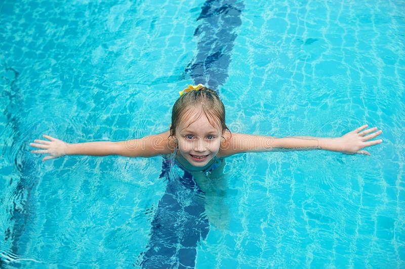 Portrait of cute happy little girl having fun in swimming pool.  Kids sport on family summer vacation. Active healthy holiday stock images