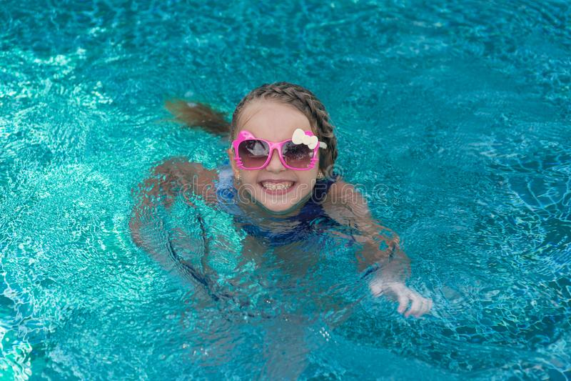 Portrait of cute happy little girl having fun in swimming pool.  Kids sport on family summer vacation. Active healthy holiday stock photos