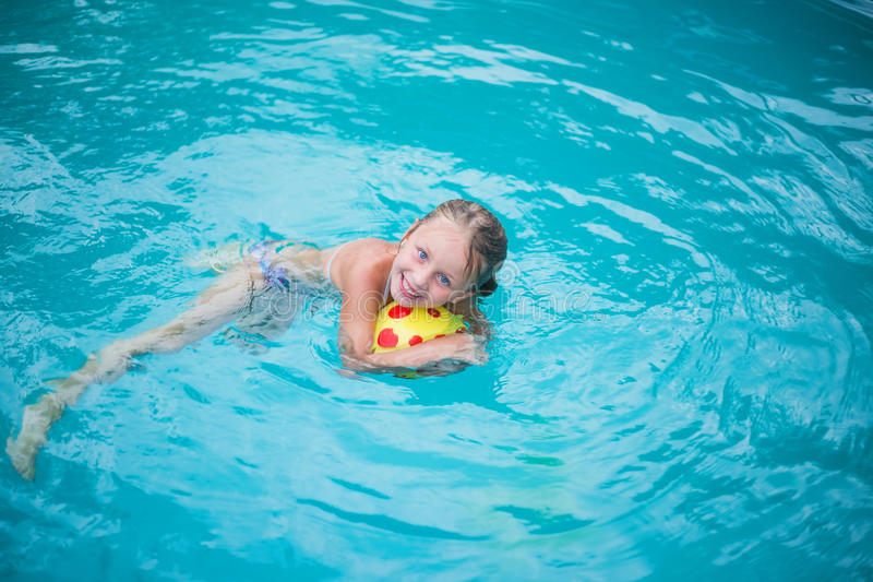 Portrait of cute happy little girl having fun in swimming pool. Kids sport on family summer vacation. Active healthy holiday. Little girl is swimming in the pool stock image