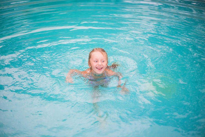 Portrait of cute happy little girl having fun in swimming pool. Kids sport on family summer vacation. Active healthy holiday. Cute little girl in the pool swims royalty free stock photo