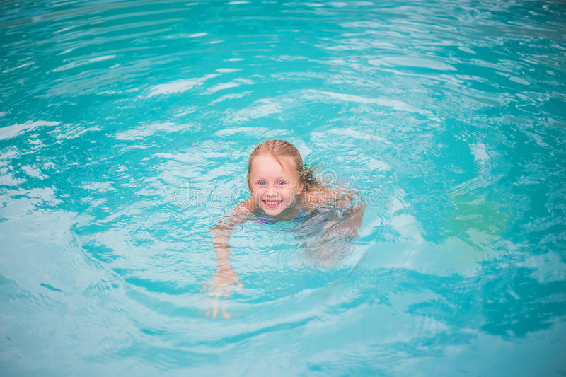 Portrait of cute happy little girl having fun in swimming pool. Kids sport on family summer vacation. Active healthy holiday. Little girl is swimming in the pool royalty free stock photos