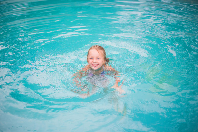 Portrait of cute happy little girl having fun in swimming pool. Kids sport on family summer vacation. Active healthy holiday. Lovely cheerful girl swimming in royalty free stock photography