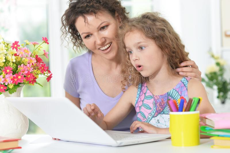 Portrait of cute happy mother and daughter using laptop stock images