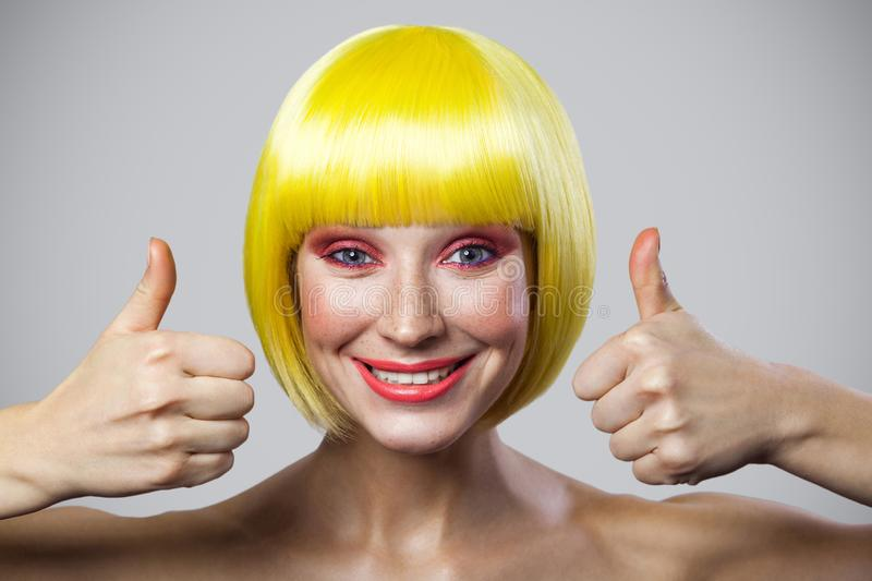 Portrait of cute happy satisfied young woman with freckles, red makeup and yellow wig, looking at camera with toothy smile and stock images