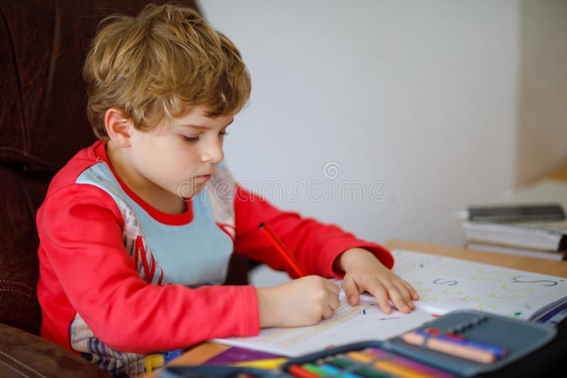 Portrait of cute happy school kid boy at home making homework. Little child writing with colorful pencils, indoors. Elementary school and education. Kid royalty free stock images
