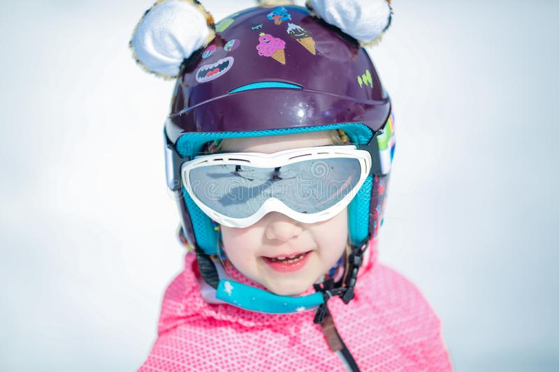 Portrait of cute happy skier girl in helmet and goggles in a winter ski resort royalty free stock photography