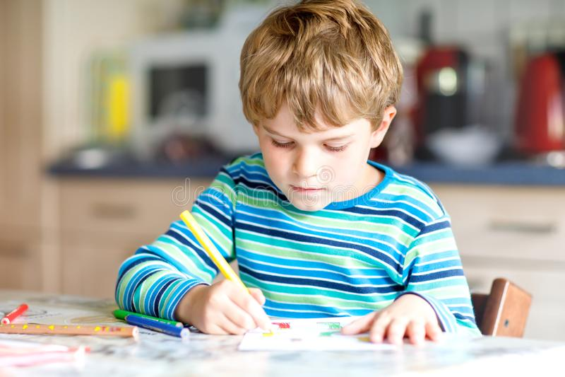 Portrait of cute healthy happy school kid boy at home making homework. Little child writing with colorful pencils. Indoors. Elementary school and education stock images