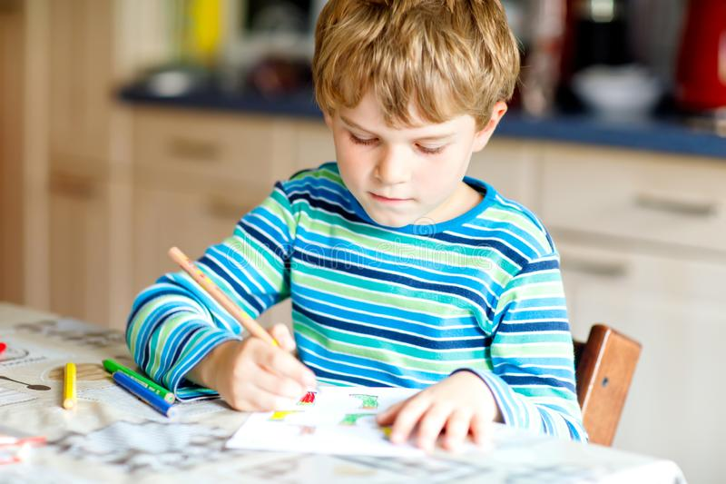 Portrait of cute healthy happy school kid boy at home making homework. Little child writing with colorful pencils. Indoors. Elementary school and education stock photos