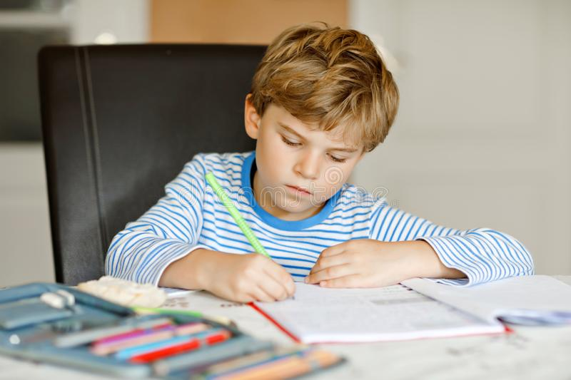 Portrait of cute healthy happy school kid boy at home making homework. Little child writing with colorful pencils. Indoors. Elementary school and education royalty free stock images