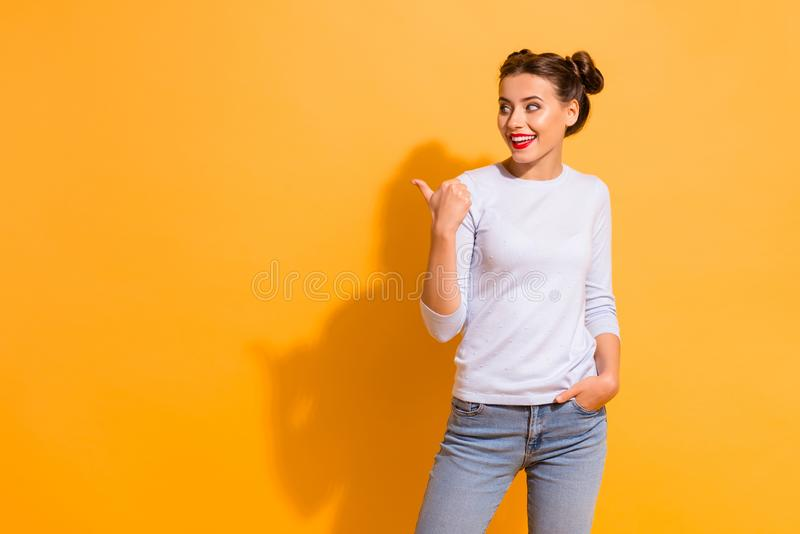 Portrait of cute isolated charming student impressed by choice decision. She is pointing at copyspace by her thumb. Dressed in white jumper blue denim clothing royalty free stock photography