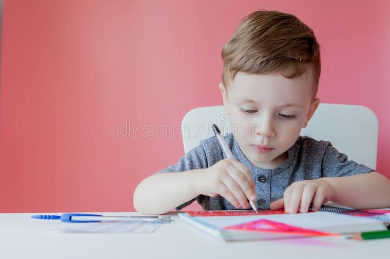 Portrait of cute kid boy at home making homework. Little concentrated child writing with colorful pencil, indoors. Elementary. School and education. Kid royalty free stock image
