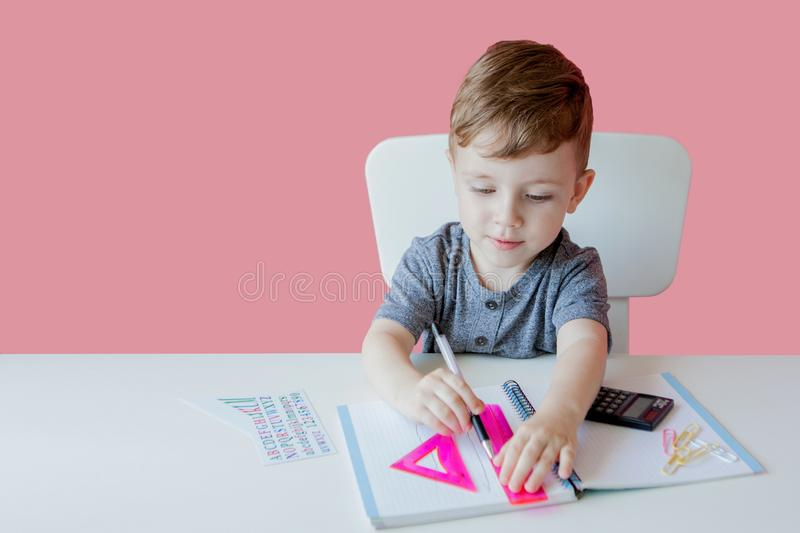 Portrait of cute kid boy at home making homework. Little concentrated child writing with colorful pencil, indoors. Elementary. School and education. Kid royalty free stock images