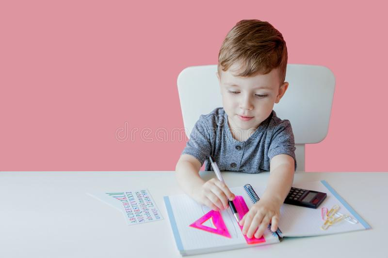 Portrait of cute kid boy at home making homework. Little concentrated child writing with colorful pencil, indoors. Elementary. School and education. Kid royalty free stock photo