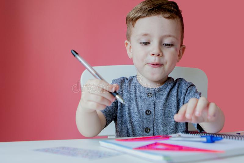 Portrait of cute kid boy at home making homework. Little concentrated child writing with colorful pencil, indoors. Elementary. School and education. Kid royalty free stock photography