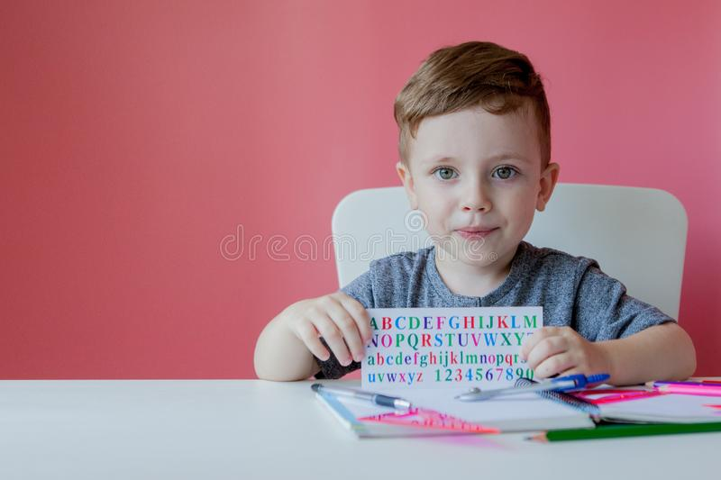 Portrait of cute kid boy at home making homework. Little concentrated child writing with colorful pencil, indoors. Elementary. School and education. Kid royalty free stock photos