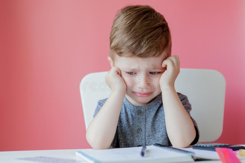 Portrait of cute kid boy at home making homework. Little concentrated child writing with colorful pencil, indoors. Elementary. School and education. Kid stock image