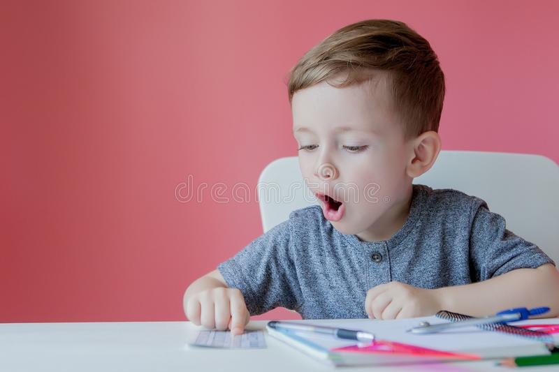Portrait of cute kid boy at home making homework. Little concentrated child writing with colorful pencil, indoors. Elementary. School and education. Kid stock photos