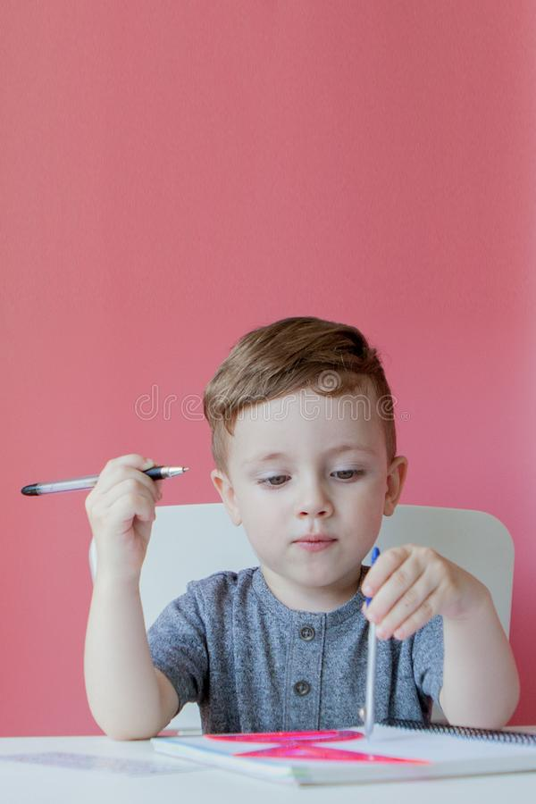 Portrait of cute kid boy at home making homework. Little concentrated child writing with colorful pencil, indoors. Elementary. School and education. Kid stock photography