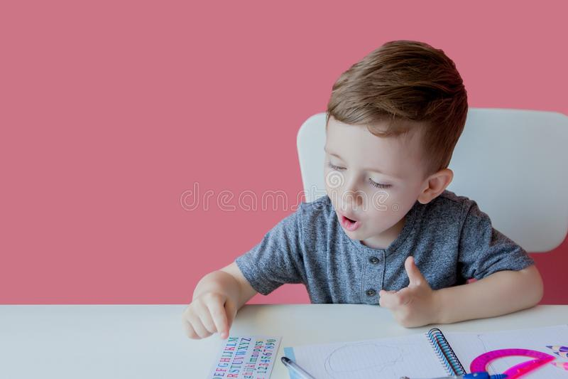 Portrait of cute kid boy at home making homework. Little concentrated child writing with colorful pencil, indoors. Elementary. School and education. Kid stock photo