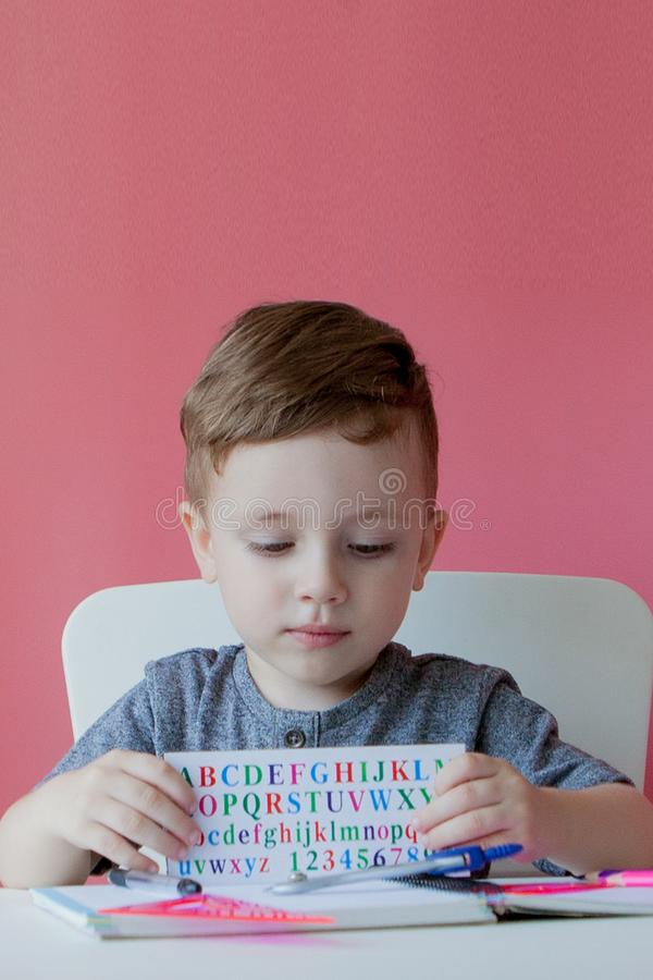 Portrait of cute kid boy at home making homework. Little concentrated child writing with colorful pencil, indoors. Elementary. School and education. Kid stock images