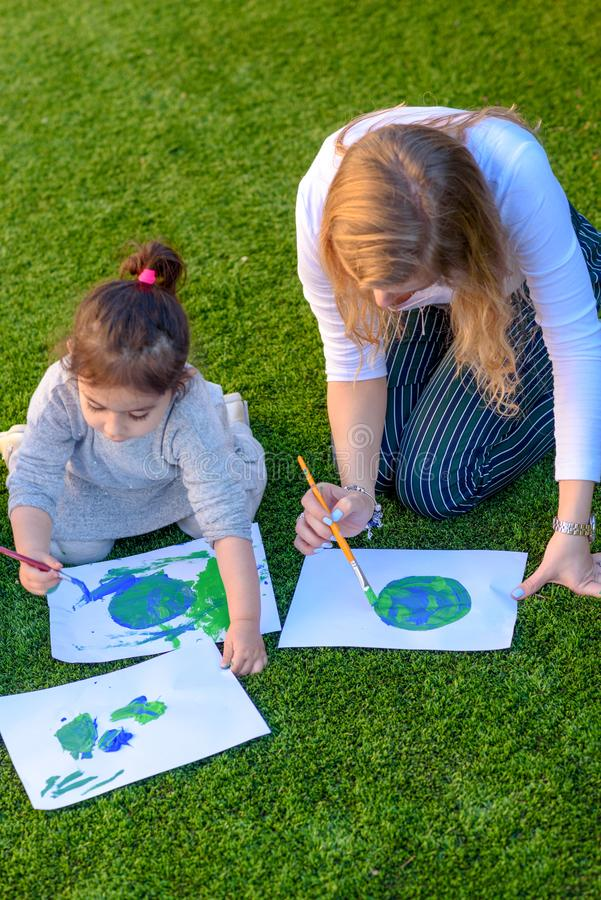 Portrait of the cute kid drawnig a picture of earth globe. stock images
