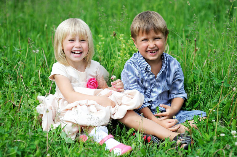 Portrait of cute kids sitting on green grass stock photo
