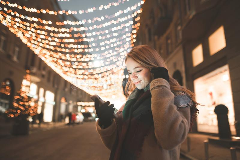 Portrait of a cute lady in warm clothes uses a smartphone, looks at the screen and smiles at an evening walk royalty free stock photos