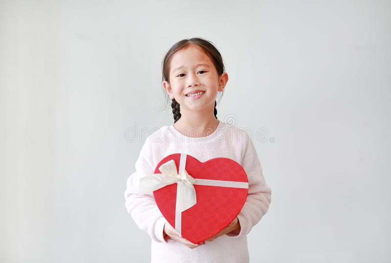 Portrait of cute little Asian child girl holding red heart gift box isolated on white background stock images