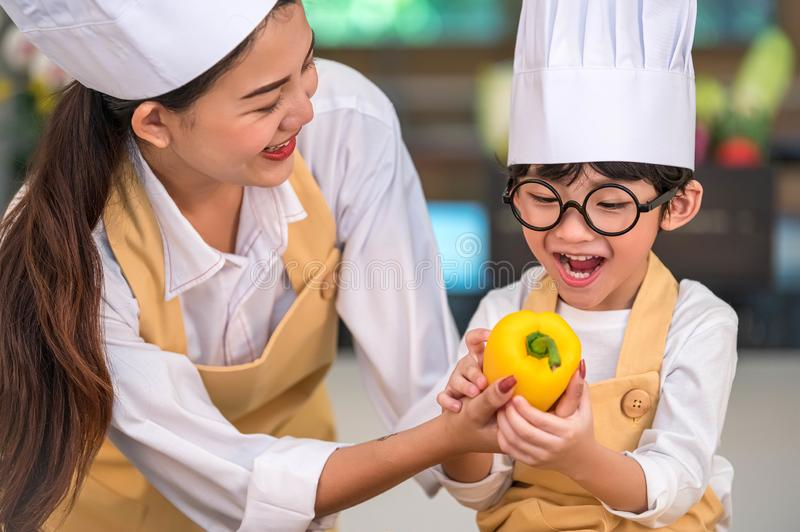 Portrait cute little Asian happy boy chef interested in cooking with mother funny in home kitchen. People lifestyles and Family. royalty free stock photo