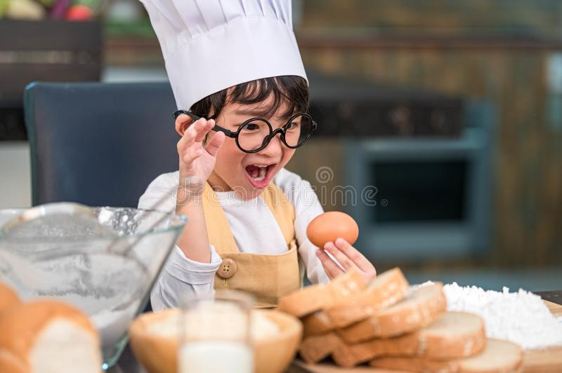Portrait cute little Asian happy boy surprised and interested in cooking funny in home kitchen. People lifestyles and Family. stock image