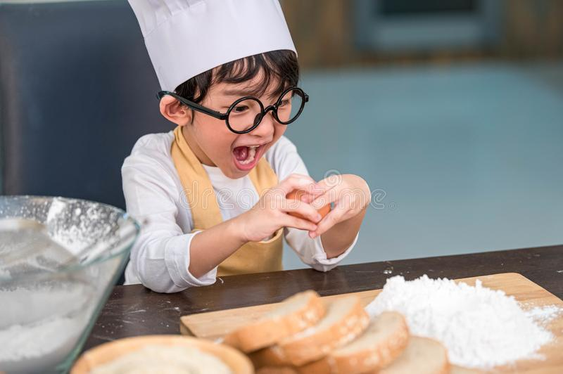 Portrait cute little Asian happy boy surprised and interested in how to break or crack egg cooking funny in home kitchen. People royalty free stock photo
