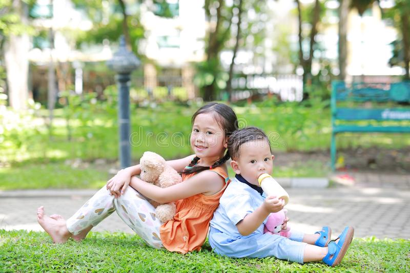 Portrait of cute little Asian sister and her younger brother sit back and lean back together in the green garden. Child girl. Cuddle teddy bear doll and boy royalty free stock photo