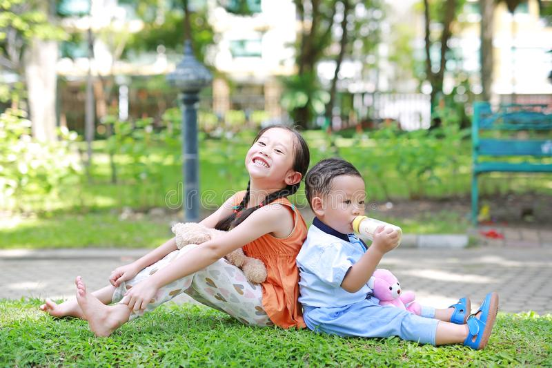 Portrait of cute little Asian sister and her younger brother sit back and lean back together in the green garden. Child girl. Cuddle teddy bear doll and boy stock images