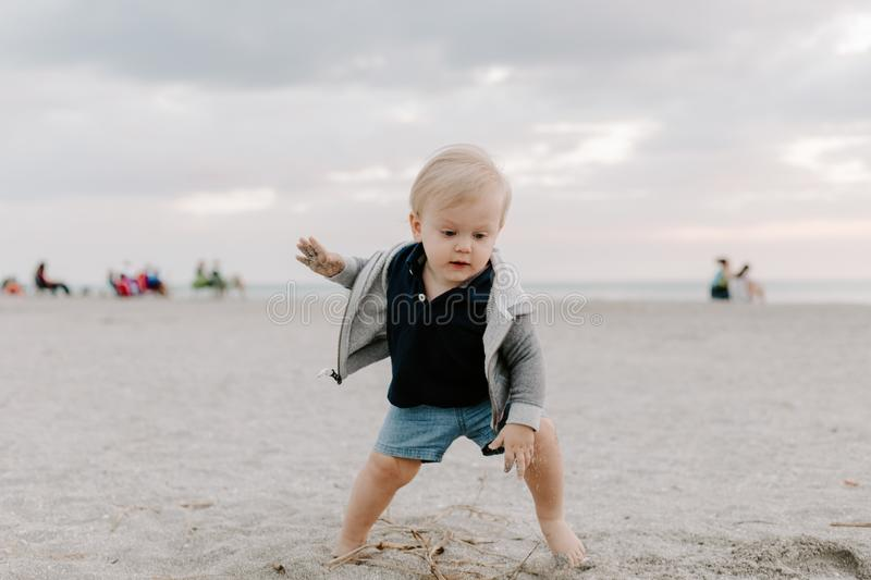 Portrait of Cute Little Baby Boy Child Playing and Exploring in the Sand at the Beach During Sunset Outside on Vacation in Hoodie stock photography