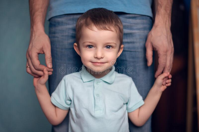 Portrait of a cute little baby smiling looking up while his father hugs him.Happy father with son royalty free stock photo