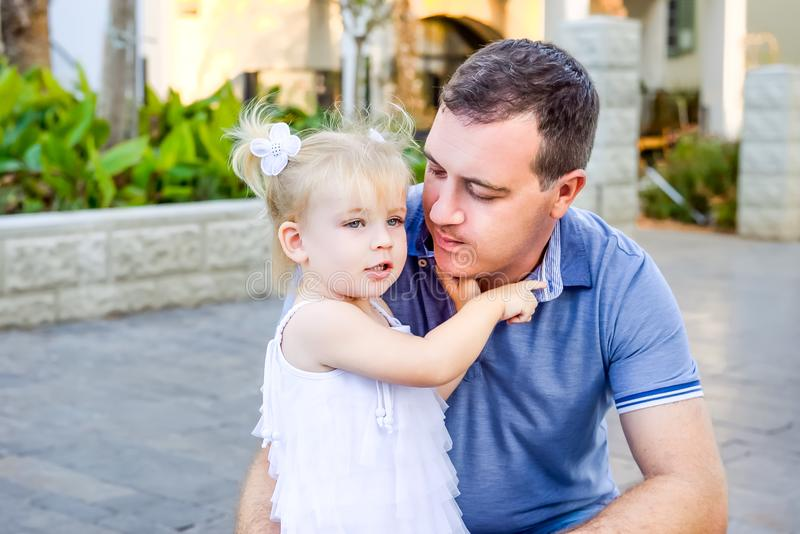 Portrait of cute little blondy toddler girl in white dress hugging her father and telling him something during walk in the city pa royalty free stock images