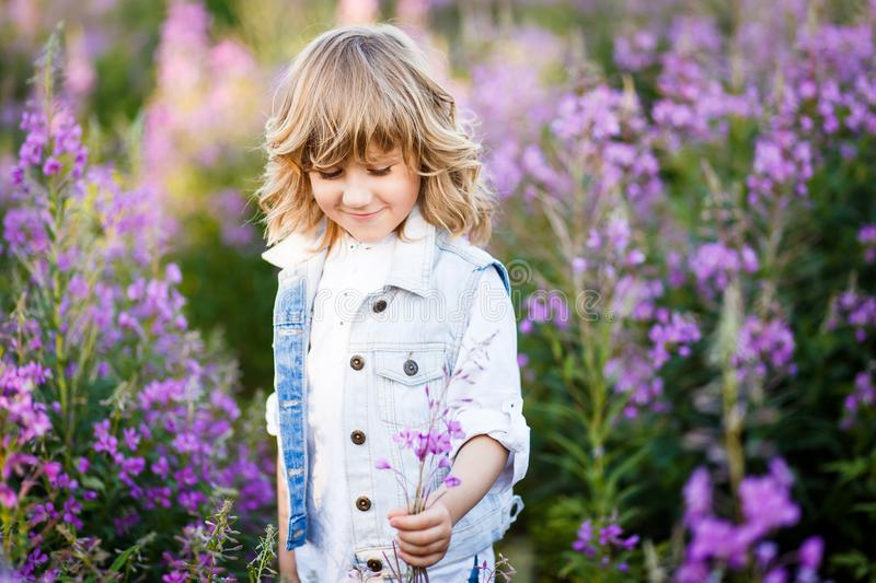 A portrait of a cute little boy with blue eyes and long blond hair outside in the field of flowers having fun stock photography