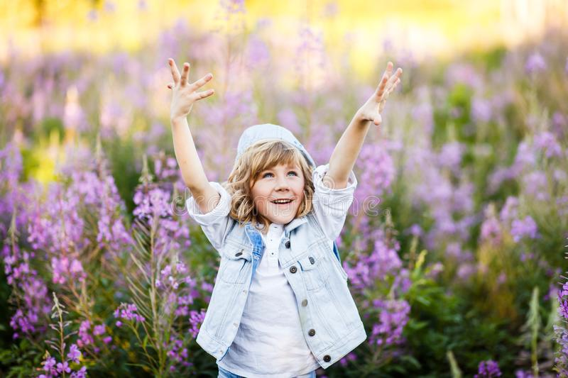 A portrait of a cute little boy with blue eyes and long blond hair outside in the field of flowers having fun royalty free stock images